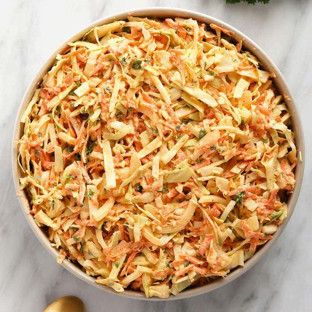 creamy coleslaw in a bowl topped with parsley