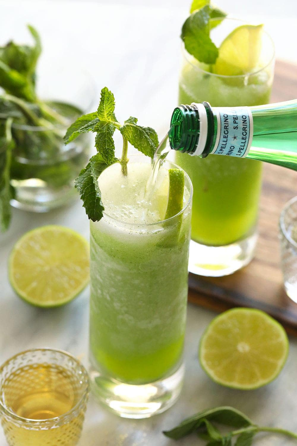 pouring sparkling water into frozen mojito