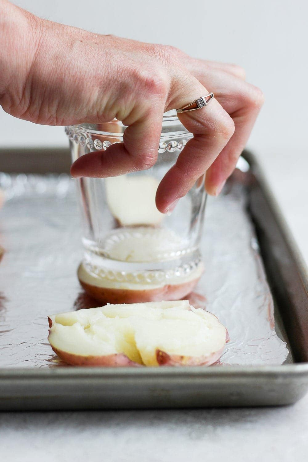 Smashing a boiled red potato with the bottom of a cup!