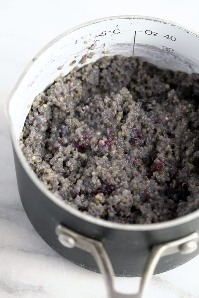 Blueberry breakfast quinoa being cooked in a pot.