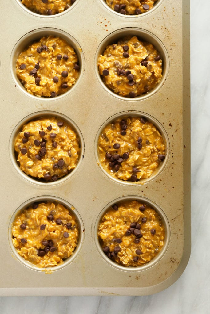 Pumpkin oatmeal cups in a muffin tin ready to go in the oven.