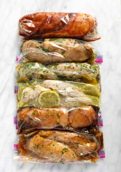 6 chicken marinades in plastic bags with chicken breasts