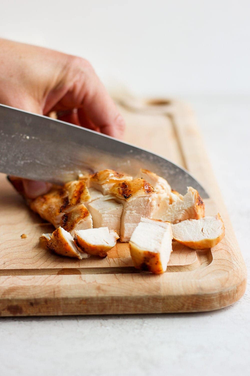 knife cutting chicken breast on cutting board
