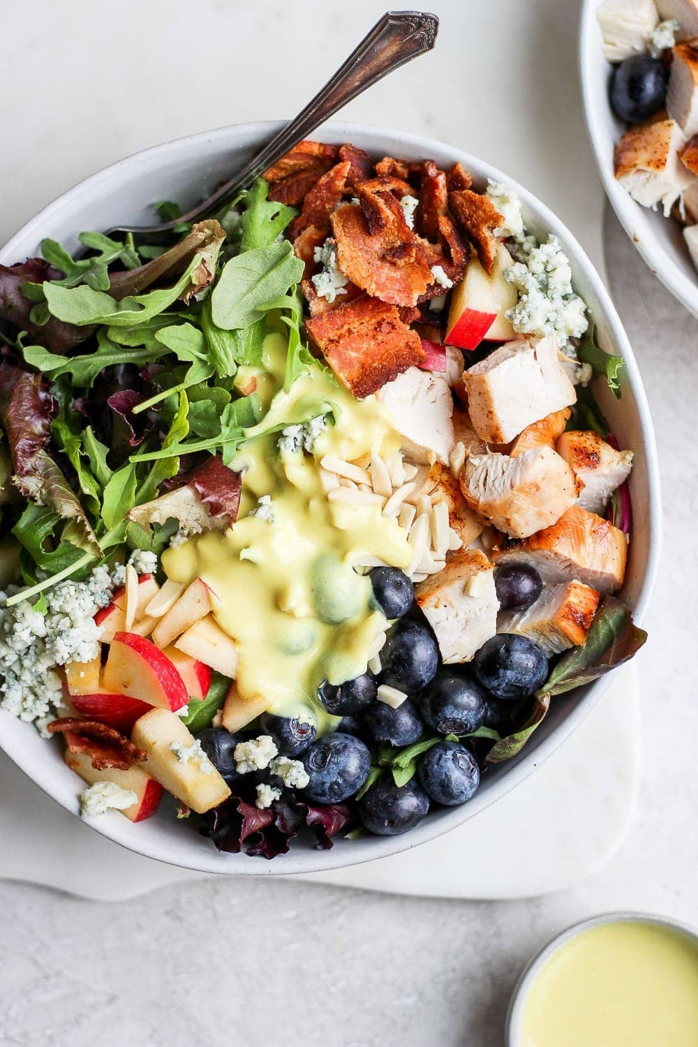 Grilled chicken salad in a bowl with small cup dressing