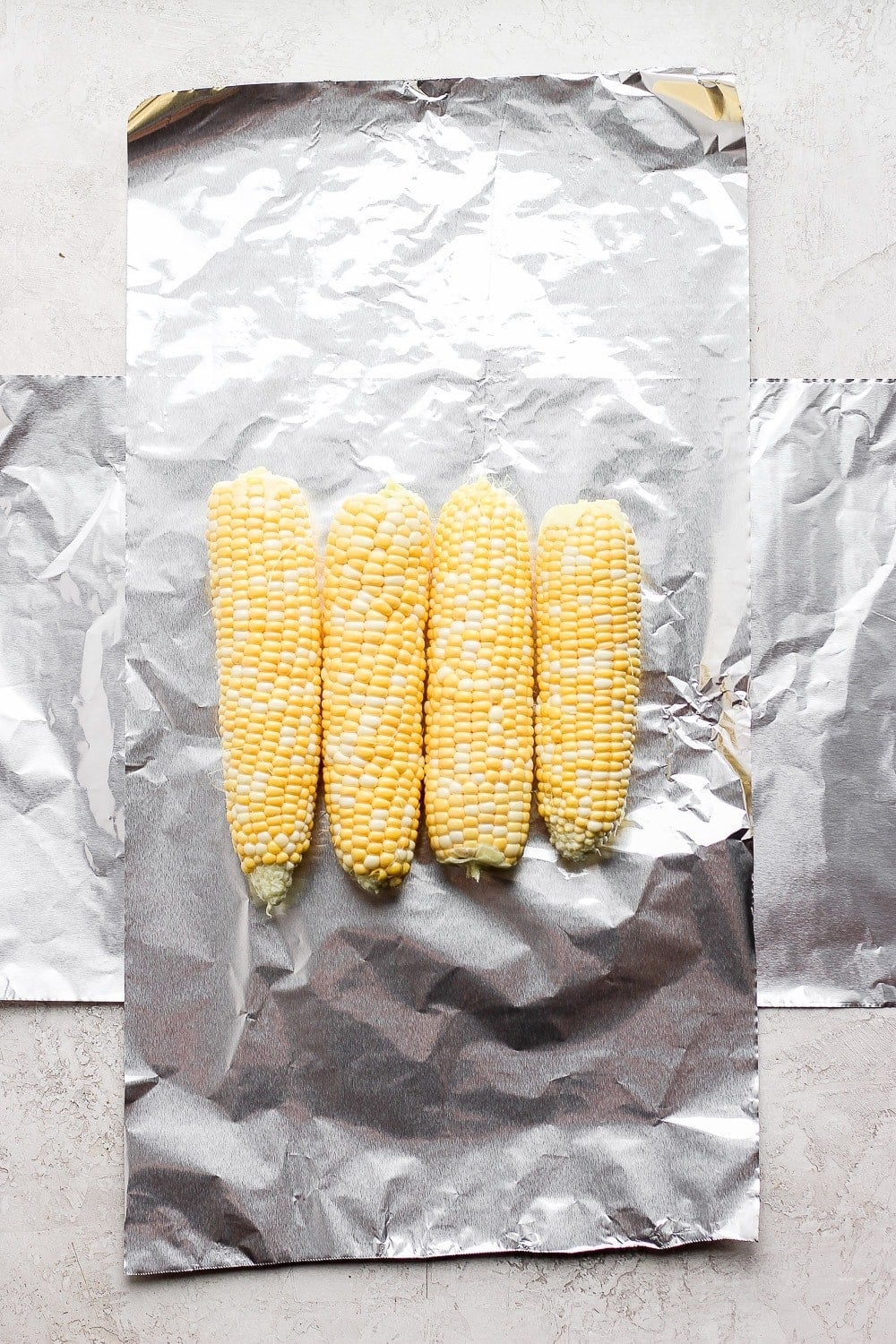 tin foil laid out with 4 ears of corn on it