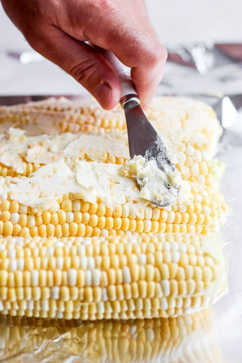 softened butter being spread on ears of corn before it goes on the grill