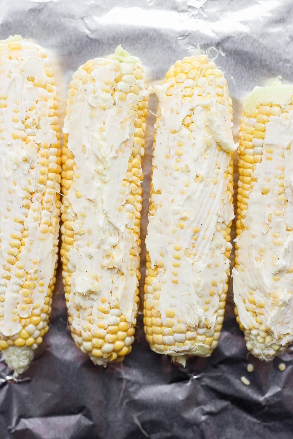 corn on the cob with butter spread on it, laid atop tin foil and ready to be made into a foil pack