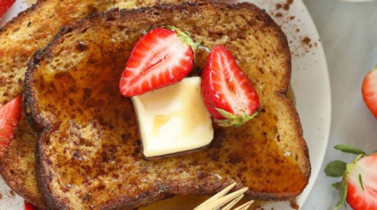 french toast topped with sliced strawberries and maple syrup