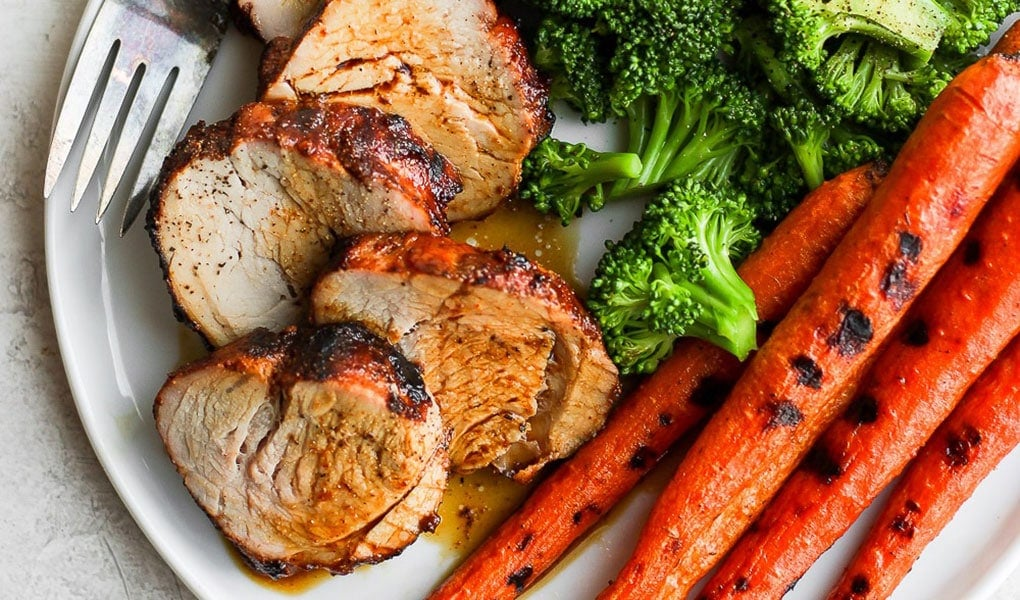 grilled pork tenderloin with carrots on plate