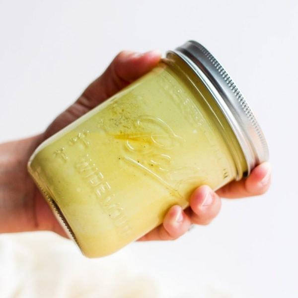 hand shaking jar of honey mustard dressing