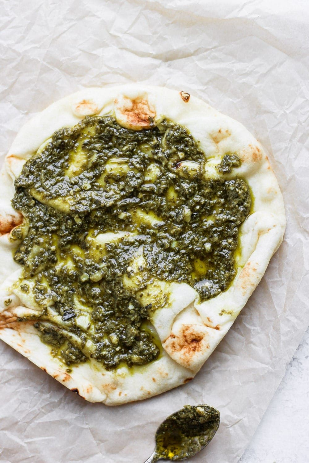 Naan pizza topped with pesto.