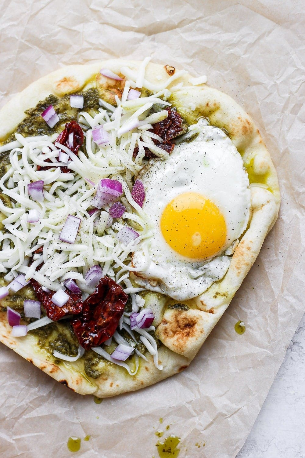 Naan pizza topped with pesto, sun dried tomatoes, cheese, and a fried egg.