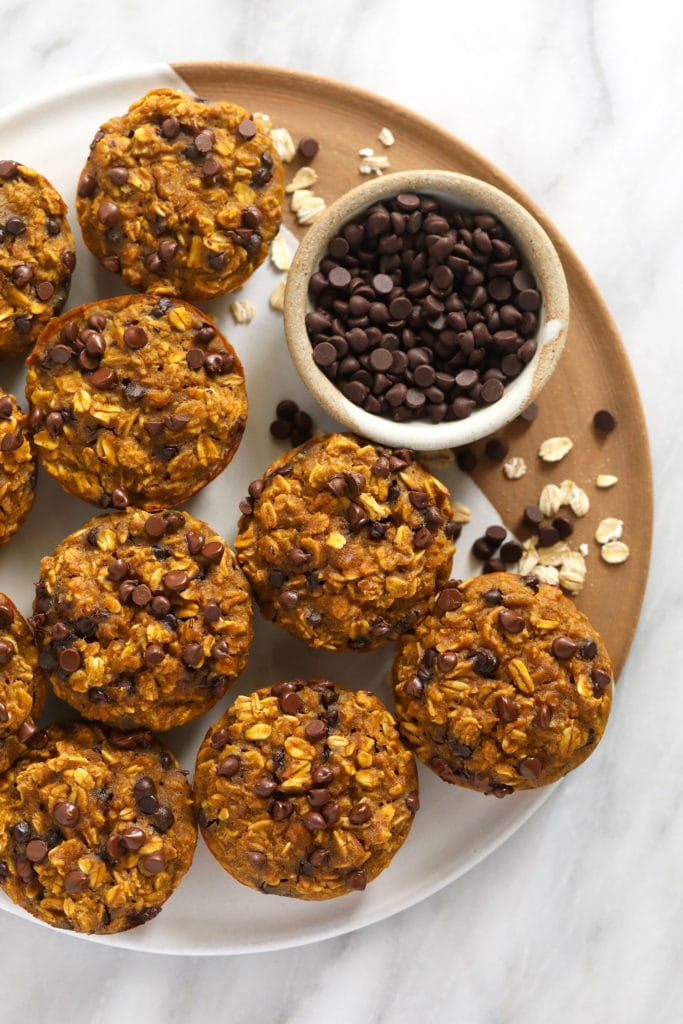 Pumpkin oatmeal cups on a tray with mini chocolate chips.