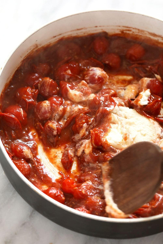 Adding ricotta to a skillet pan to make the tomato sauce creamy.