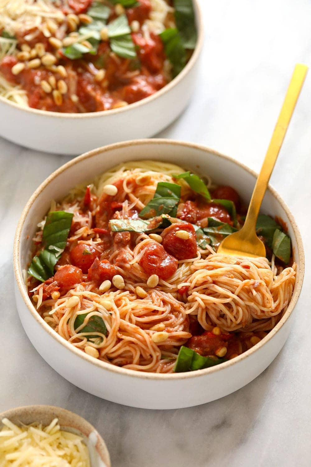 Two bowls of garden summer pasta with fresh basil on top.