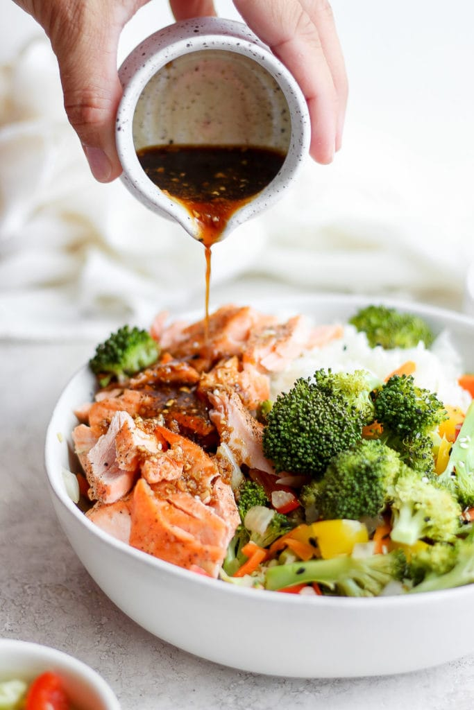 sauce being poured over sheet pan salmon stir fry in a bowl