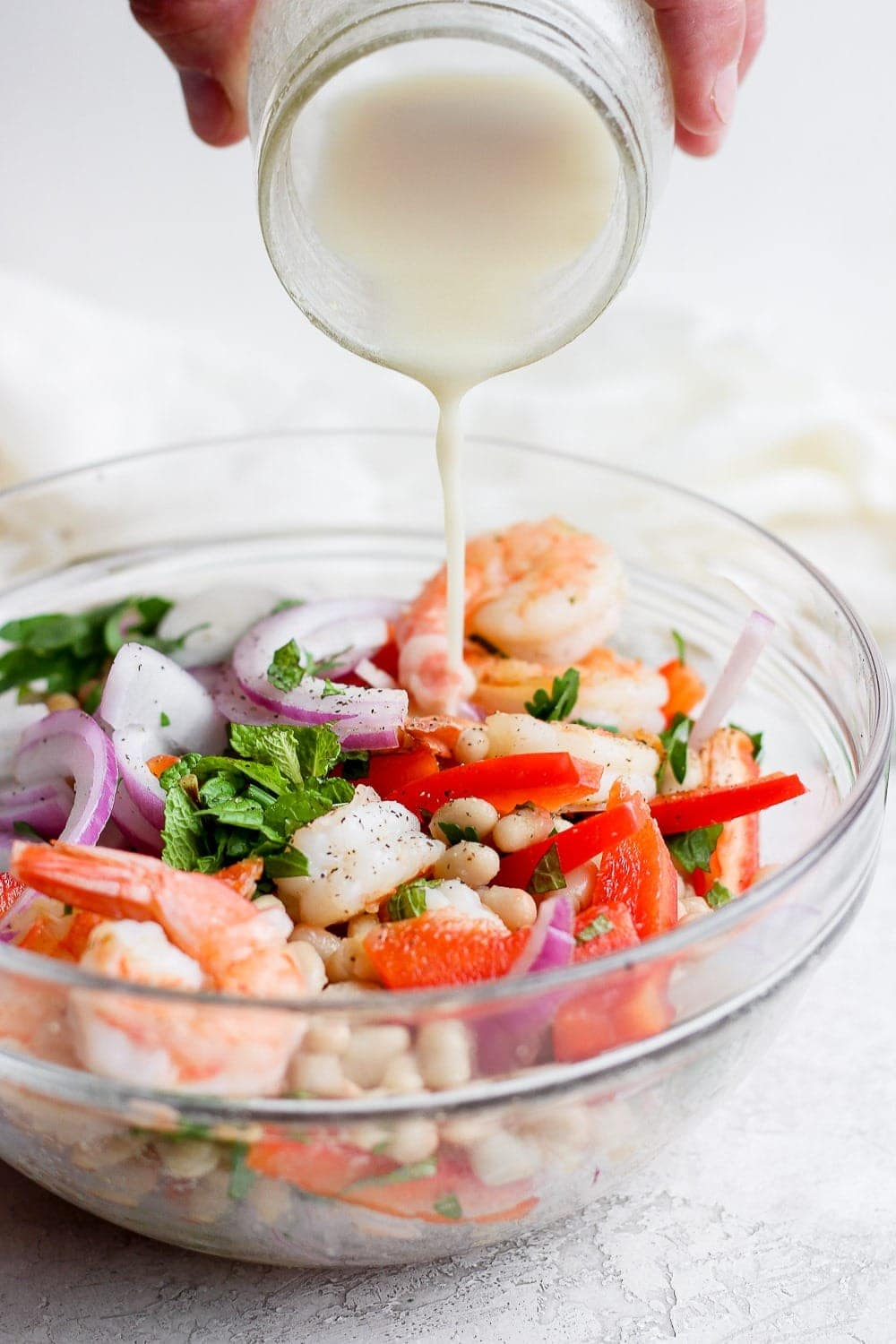 creamy dressing being poured over healthy shrimp salad