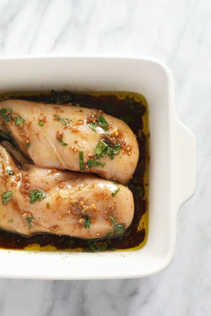 Raw chicken marinating in a pan.