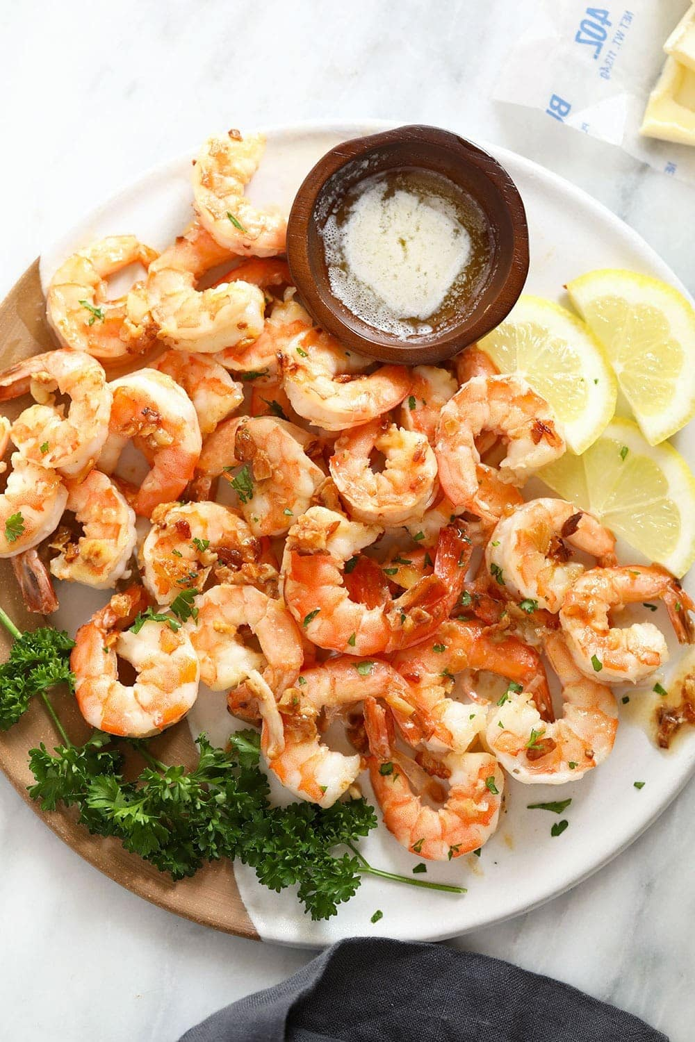 garlic butter shrimp on a plate with butter for dipping