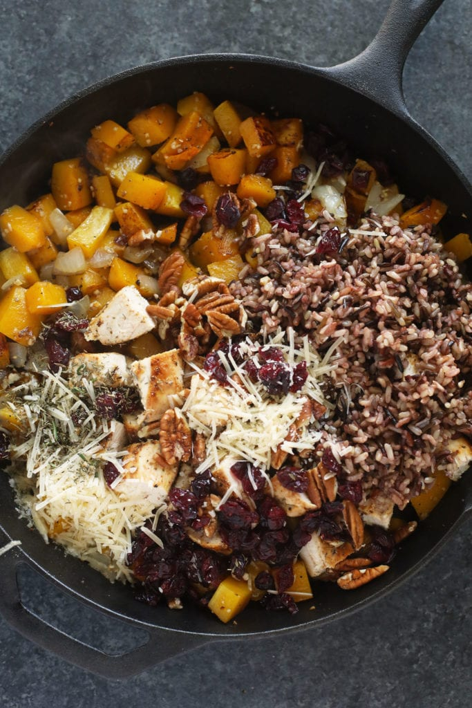 butternut squash wild rice casserole in a cast iron pan ready to be mixed together and baked