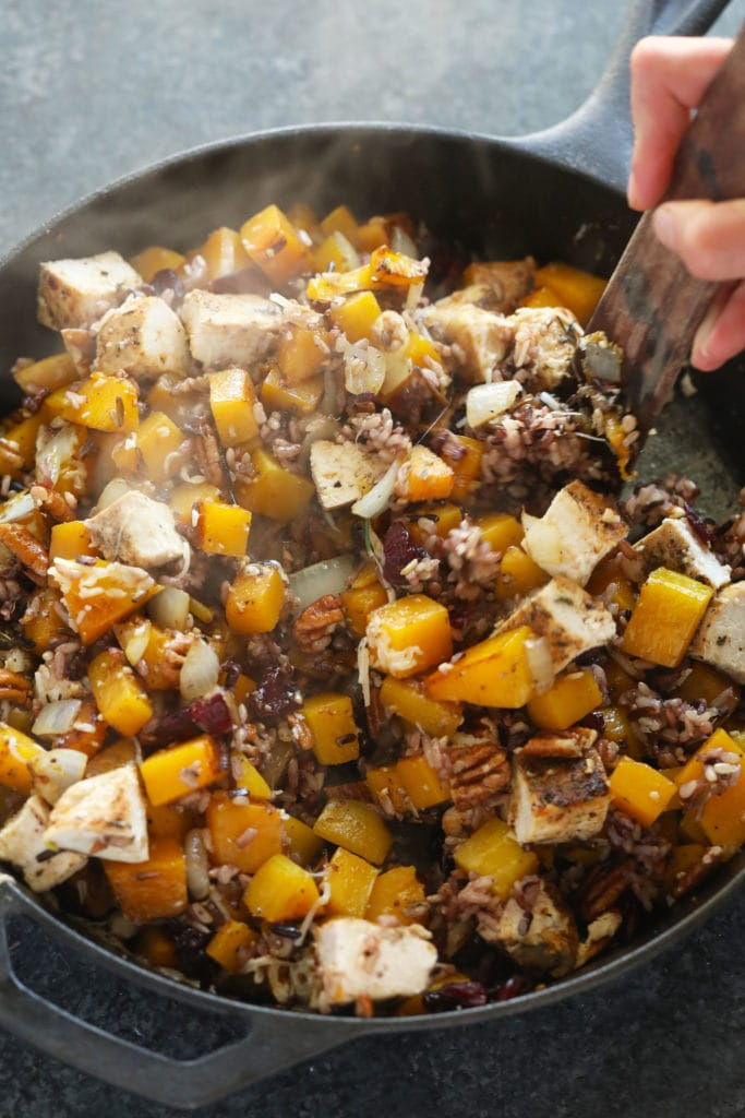 butternut squash wild rice casserole ingredients being mixed together in a cast iron pan