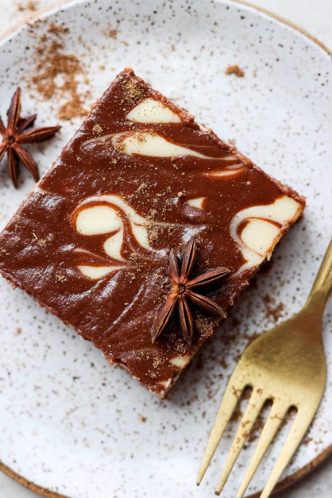 A chocolate chai cheesecake bar on a plate.