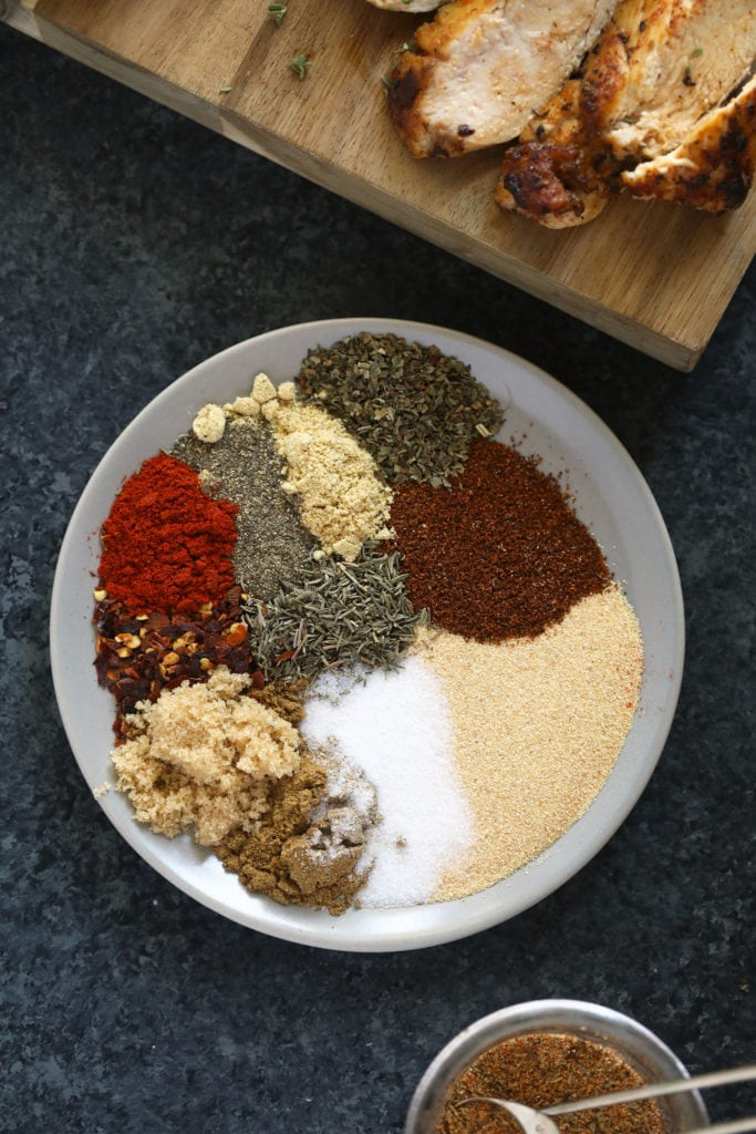All of the different dried spices or herbs on a plate.