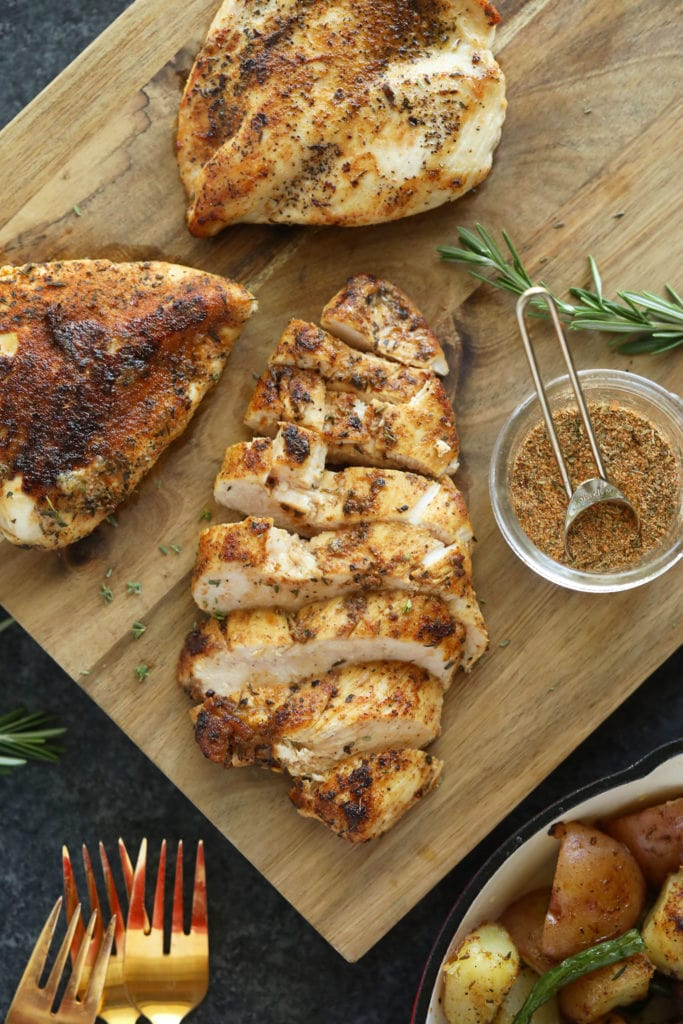 Season and baked chicken breast on a cutting board.