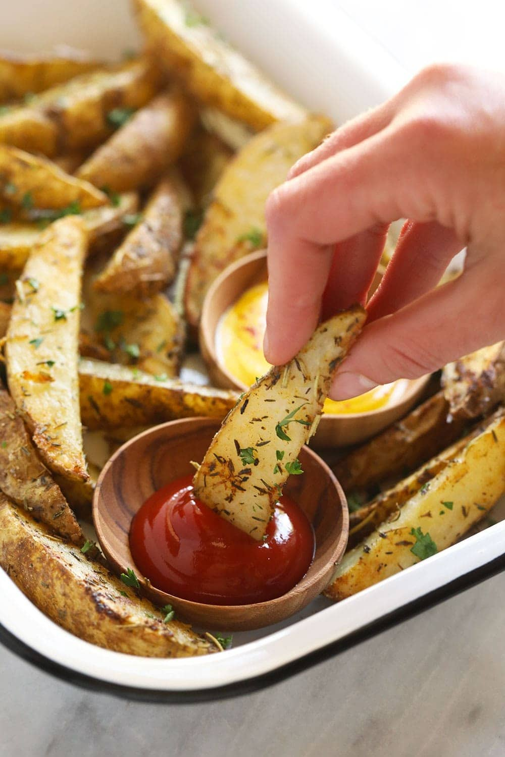 Dipping a potato wedge into ketchup.