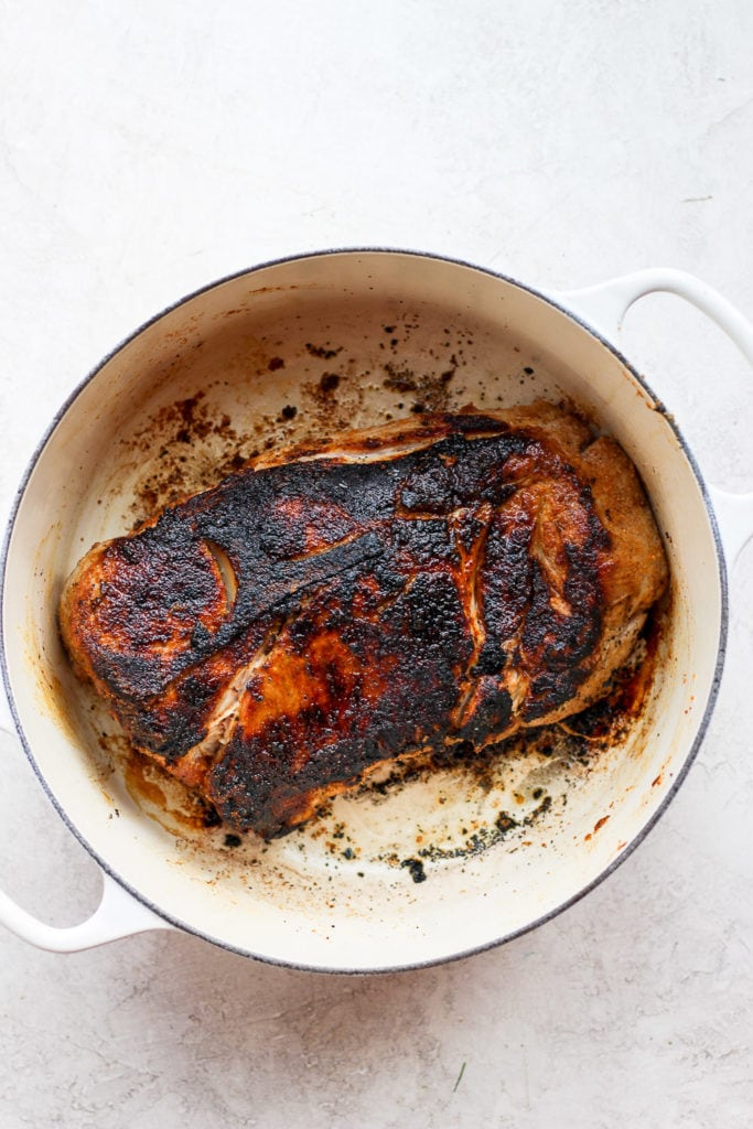 seared pork shoulder in a stock pot