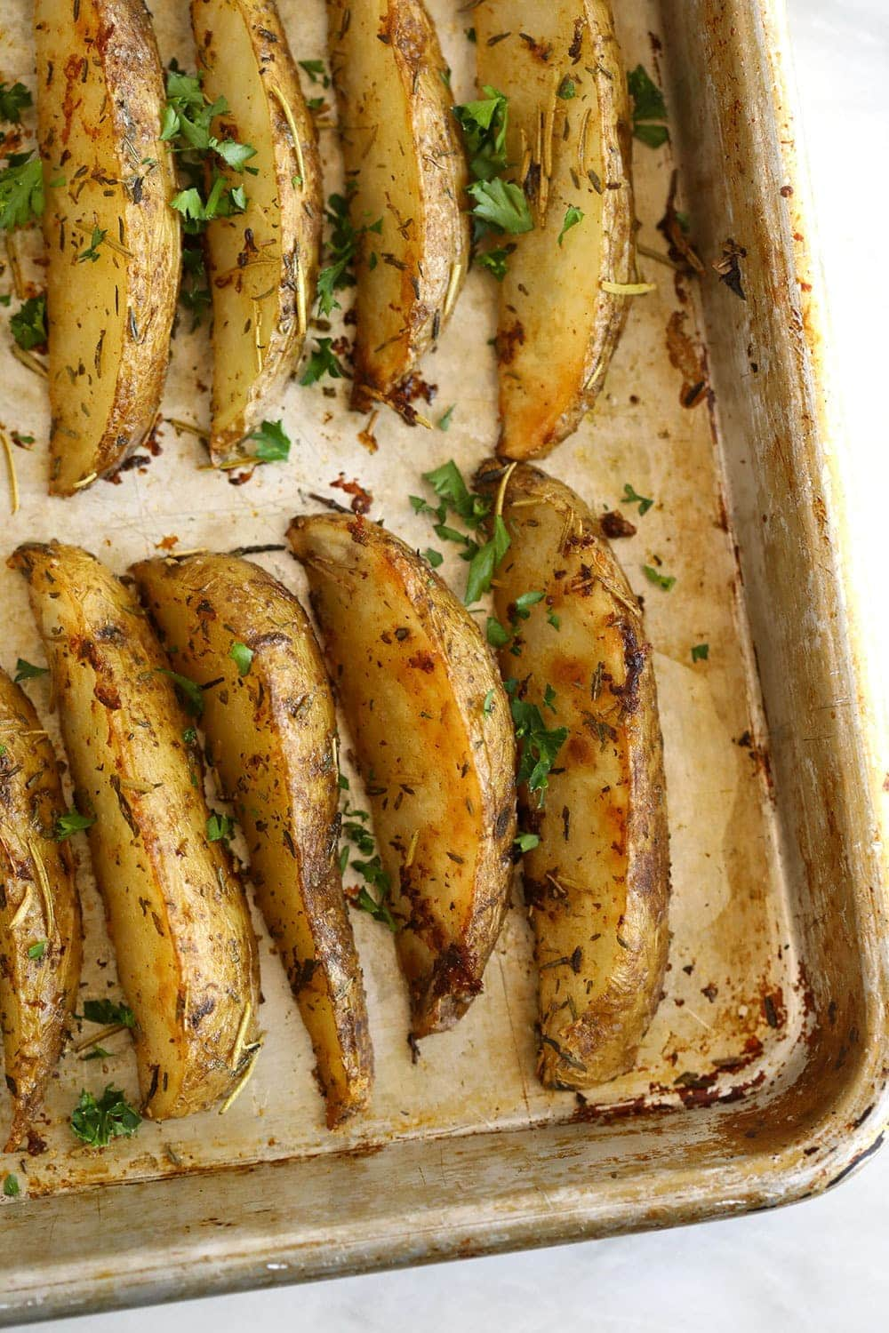 Potato wedges on a baking sheet with fresh parsley sprinkled over the potato wedges.