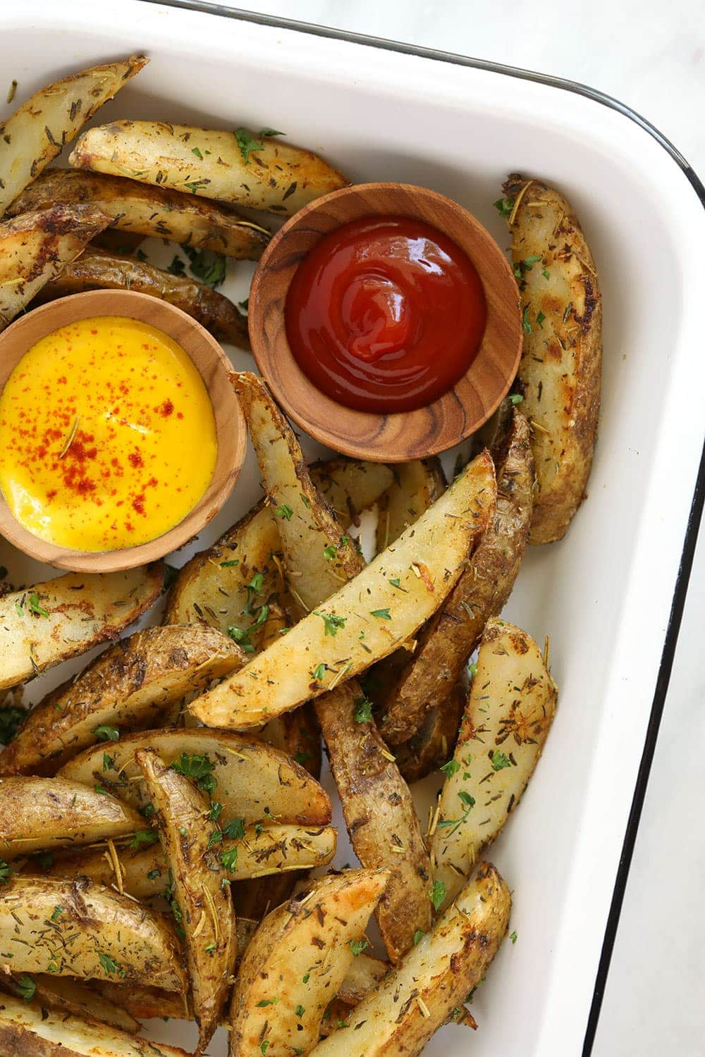 Potato wedges in a pan with ketchup and mustard.