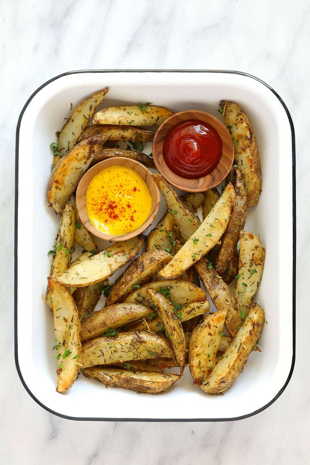 Potato wedges in a platter with ketchup and mustard.