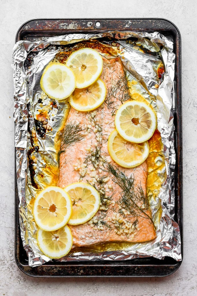 large salmon fillet on tin foil with lemons