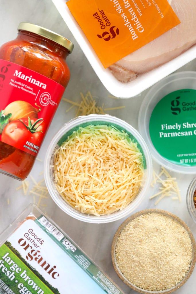 chicken parm ingredients - parmesan cheese, marinara sauce, and chicken breast