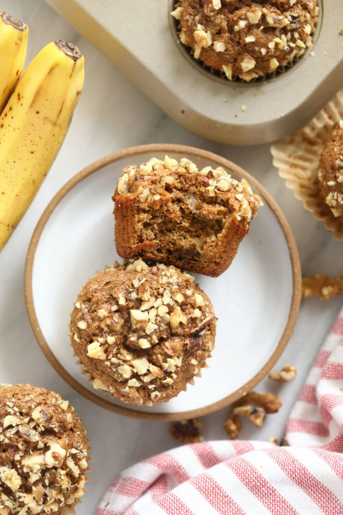 Two banana and nut muffins on a plate.
