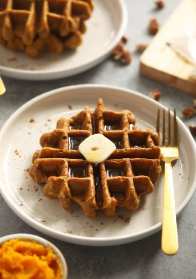 pumpkin waffle on plate with fork and butter