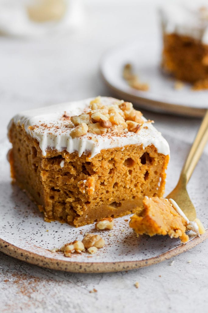 slice of pumpkin sheet cake on a plate with a bite ready to eat on a fork