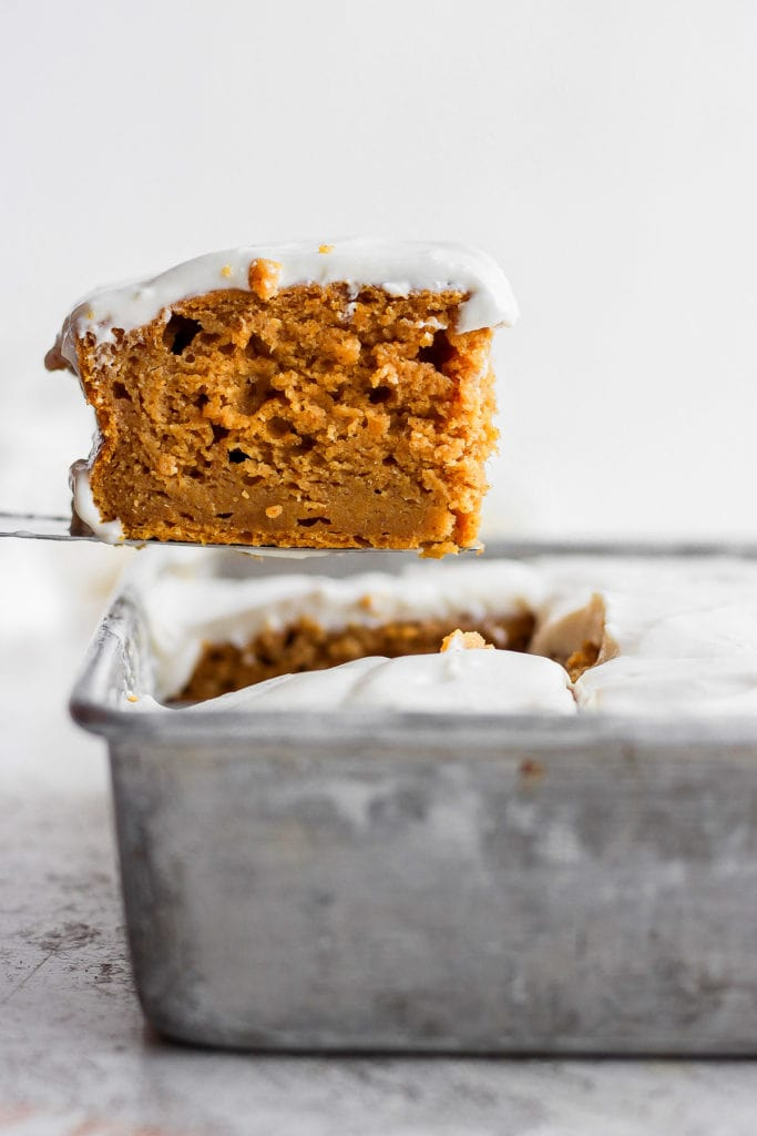 slice of pumpkin sheet cake coming out of the pan