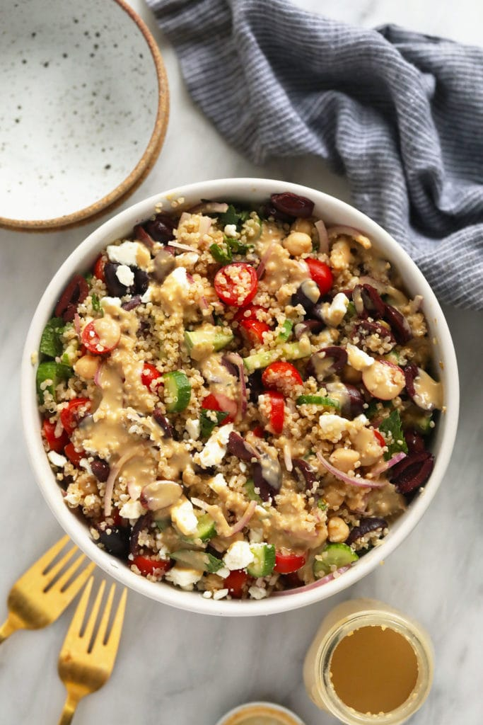 quinoa salad in bowl with hummus dressing