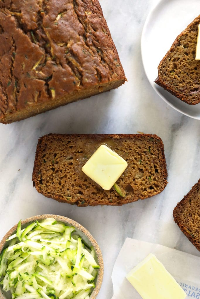 Zucchini bread on a plate with a tab of butter.