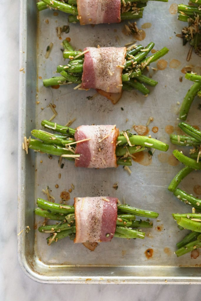 bacon wrapped green beans ready to be baked on a baking sheet