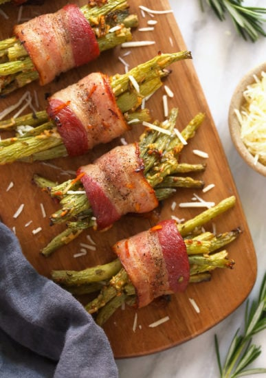 bacon wrapped green beans on a wooden platter