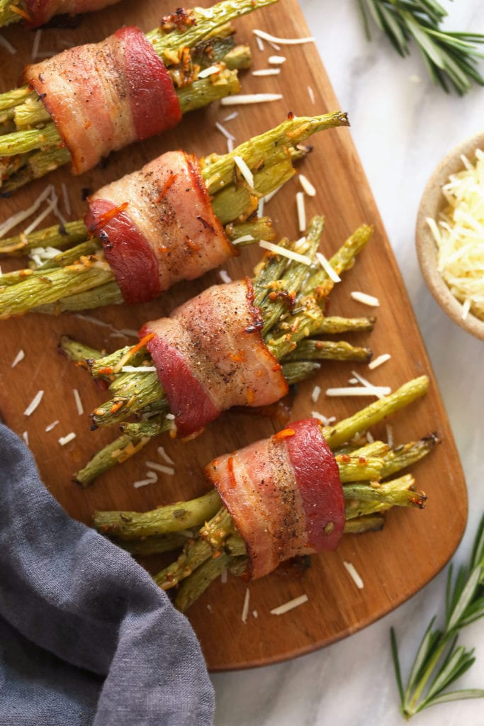 bacon wrapped green beans served on a wooden platter