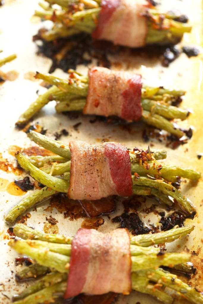 bacon wrapped green beans on a baking sheet