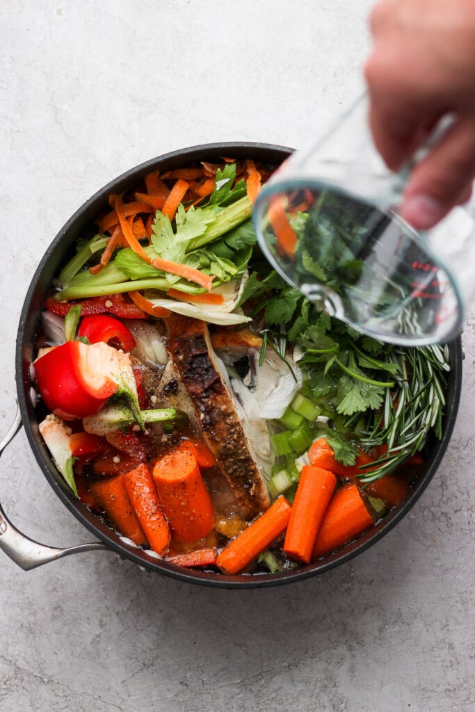 Pouring water into a pot full of vegetables.