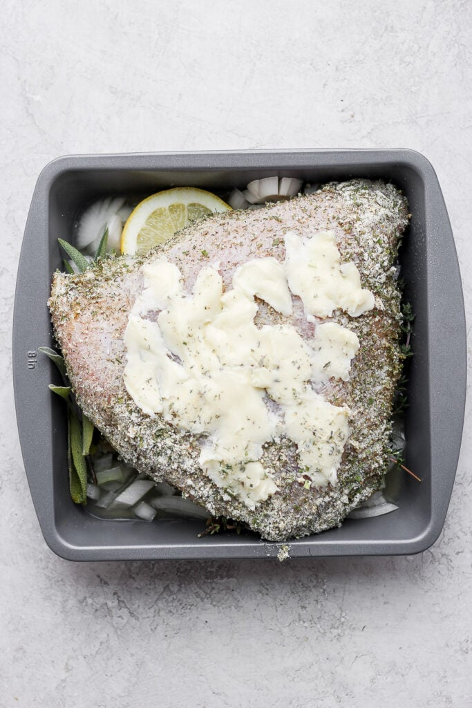 Butter, herbs, and a turkey breast in a baking dish.