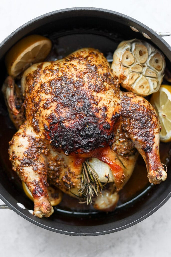 whole roasted chicken with garlic in pan