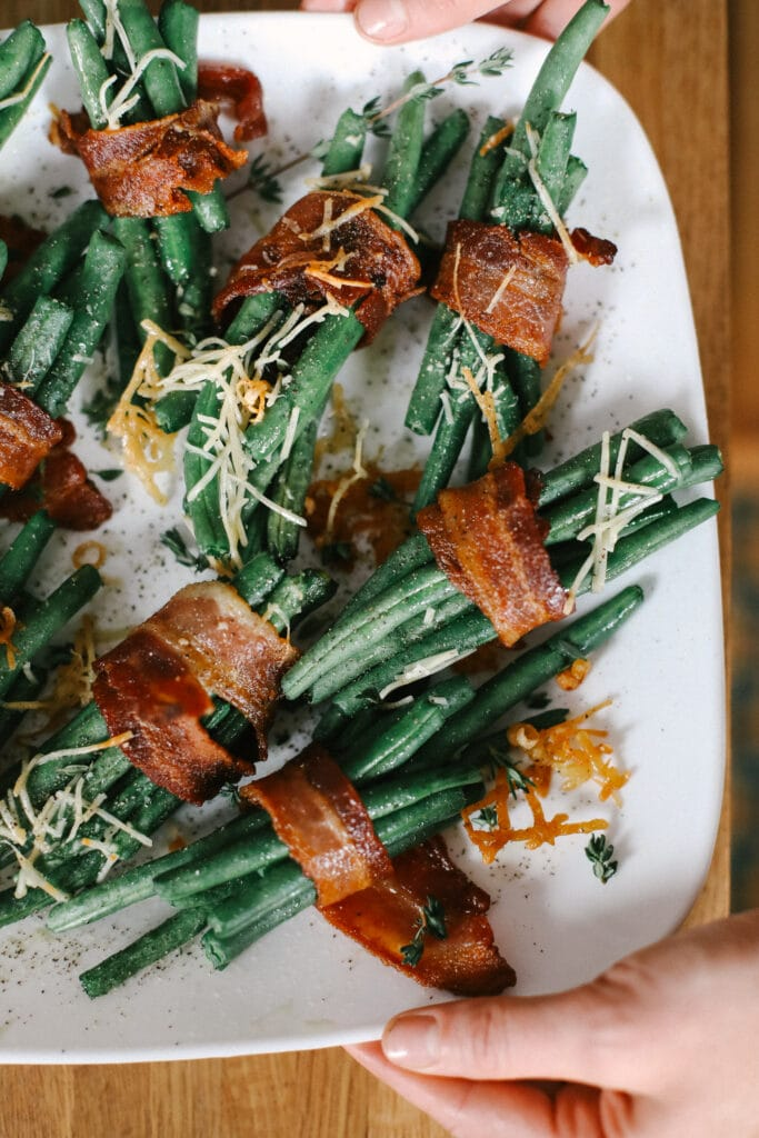 bacon wrapped green beans on a plate topped with parmesan cheese