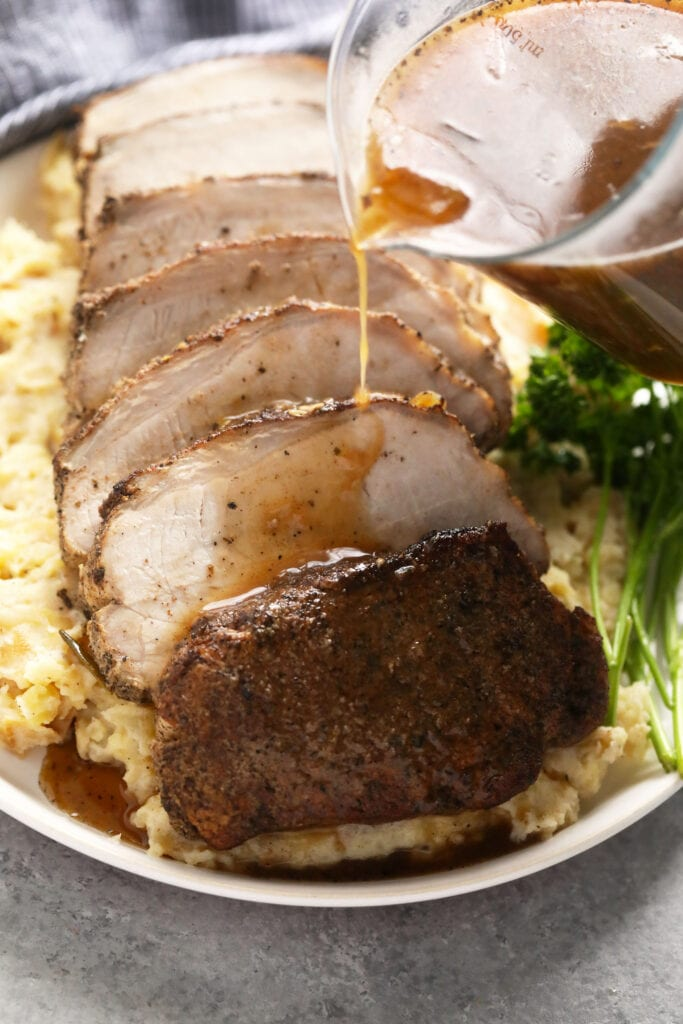 slow cooker pork loin sliced on a bed of mashed potatoes